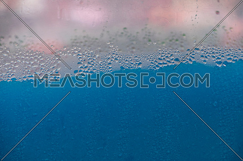Close up background of blue slush ice smoothie drink in machine canister, low angle side view