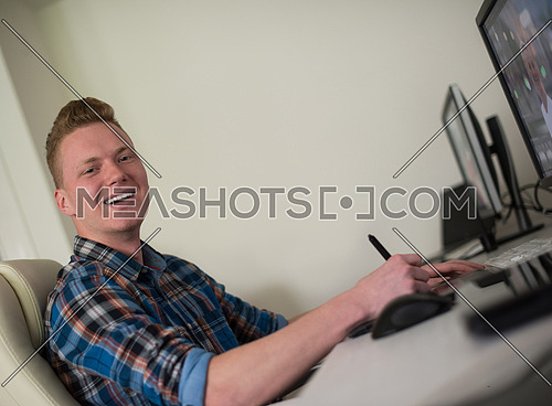 Young graphic designer working on a digital tablet and a computer