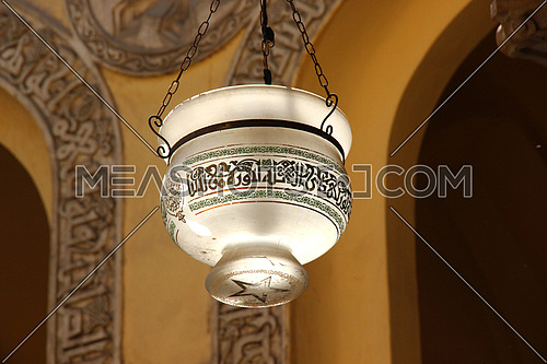 a photo from inside AL Aqmar mosque in Islamic Cairo, Egypt  showing part of the ceiling and traditional lamp post used for lighting at that time
