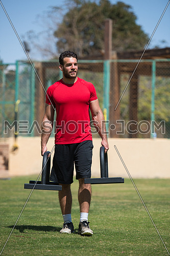 Portrait of a young middle eastern Athletic-built man in the external field of fitness which is preparing for exercise