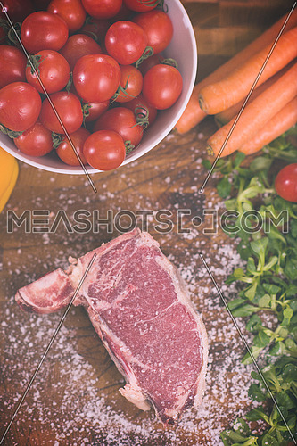 Juicy slice of raw steak with vegetables around on a wooden table top view