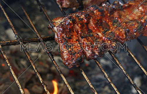 Rack of pork spare ribs cooked on fire barbecue grill, close up, high angle view