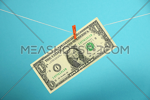American economy growth, strengthening of US dollar illustrated, one dollar banknote hanged ascending with pin at rope over blue background