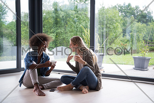 Two young laughing multiethnic women sit on the floor near the window and enjoy while drinking coffee using smartphone in luxury home