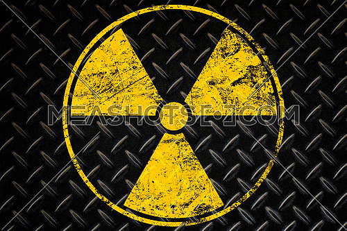 Yellow radioactive hazard warning sign painted over grunge black metal wall background with copy space