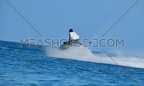 One young man riding jet ski scooter over blue sea water with splash trace behind, low angle rear side view