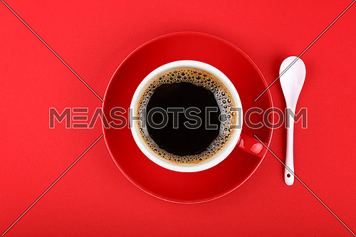 Close up one full cup of black Americano coffee and saucer ith white spoon over vivid red paper background, elevated top view, directly above
