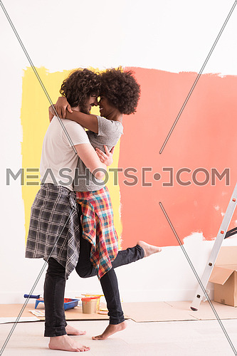 Young happy multiethnic couple hugging while they painting a wall in their new home