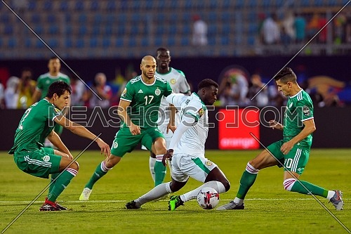 27 June 2019, Egypt, Cairo: Senegal's and Algeria's players battle for the ball during the 2019 Africa Cup of Nations Group C soccer match between Senegal and Algeria at the 30 June Stadium.