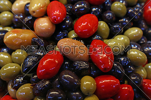 Mix of assorted whole Italian olives (black, green, red) in oil close up, retail market stall display, low angle view