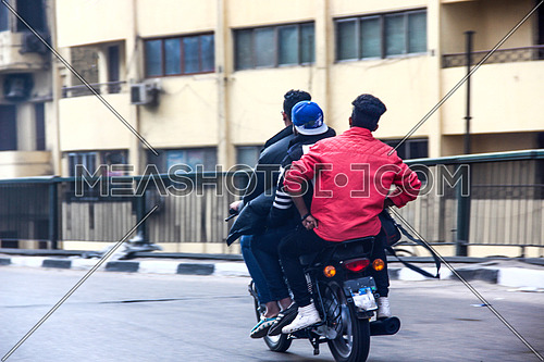 a photo from a bridge ,Cairo streets , Egypt showing three young men driving a motorbike