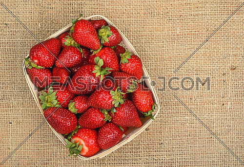 Strawberry in wooden basket on jute canvas