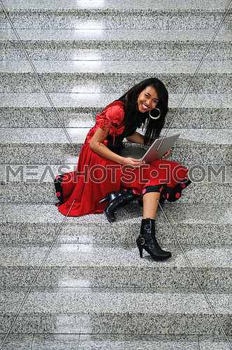 young business woman working wireless on laptop at indoor staircase