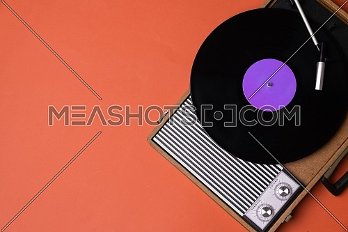 Vintage vinyl player and turnable on a orange background. Entertainment 70s. Listen to music. Top view.
