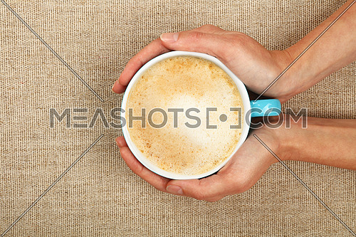 Two woman hands holding embracing big latte cappuccino coffee blue cup over linen canvas background
