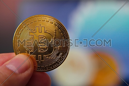 Close up shot for male hand holding bitcoin, blurry color background