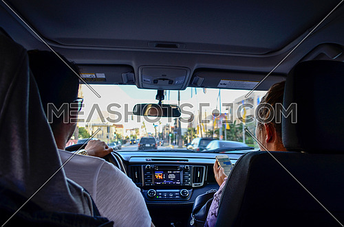 Two people in the front seats of a car, the husband driving and wife is checking her sell phone while listing to some music