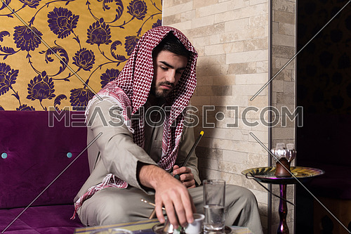 Islamic Man Smoking The Traditional Hubble-Bubble Or Hookah While Drinking Coffee