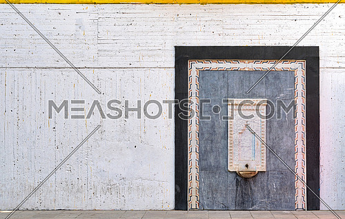 Old white marble water fountain framed by ornate marble frame and black marble frame over white concrete grunge wall, Cairo, Egypt