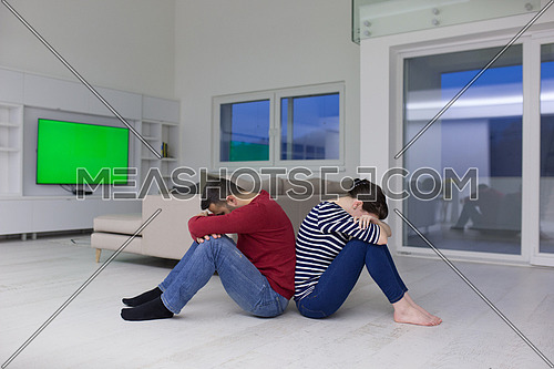 Cheerful young couple sitting with back to each other on floor at home