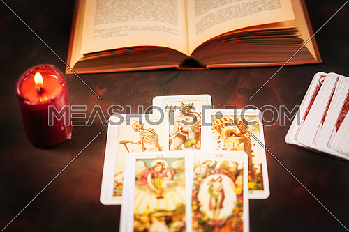 View from above of tarot cards with candlelight and book on the darkness background,Halloween and future reading concept.