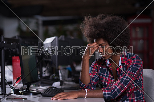 Young successful African American beautiful woman feels tired in a large modern office