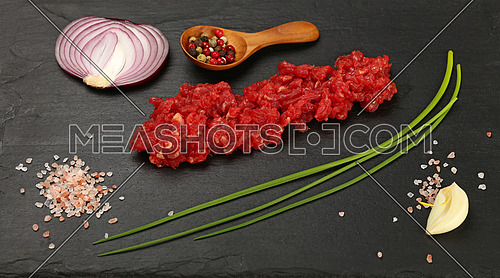 Raw minced beef red meat cutlet, spices, peppercorn in wooden scoop, spring green chive, onion, garlic cloves and Himalayan salt on black slate board, close up, high angle view