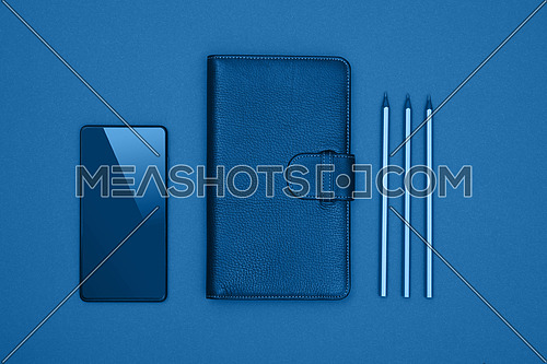 Close up one closed leather cover notebook, pencils and smartphone over blue paper background, flat lay, directly above