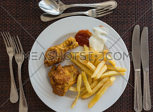Pictured fried chicken with chips served on white dish at the restaurant, view from above.