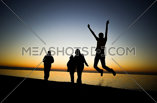 Four friends standing and jumping and having fun at the beach enjoying the golden hour by sunset