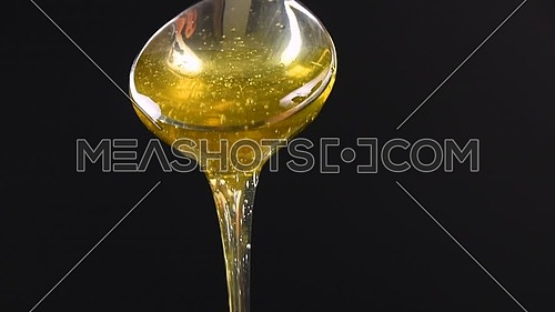 Close up fresh thick fluid acacia honey pouring and flowing from metal spoon over black background with copy space, low angle side view, slow motion