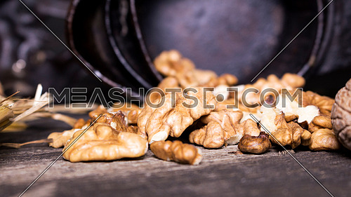 Walnuts and hand walnuts grinder on a wooden surface