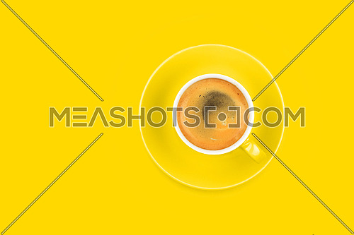 One full espresso coffee cup with saucer over vivid yellow paper background, elevated top view, directly above