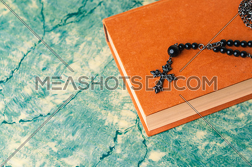 Black rosary and cross resting on the closed book at green table, seen from above.religion school concept.Vintage style.