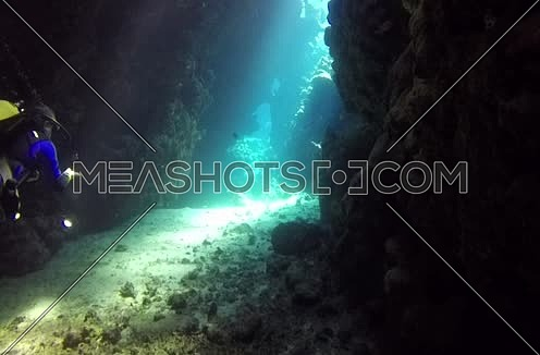 long shot for sun rays coming through rocks and coral and A diver going inside shot underwater at the Red Sea