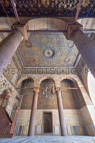 Ornate ceiling with blue and golden floral pattern decorations framed by huge arch and two columns at Sultan Barquq mosque, Al Moez Street, Old Cairo, Egypt