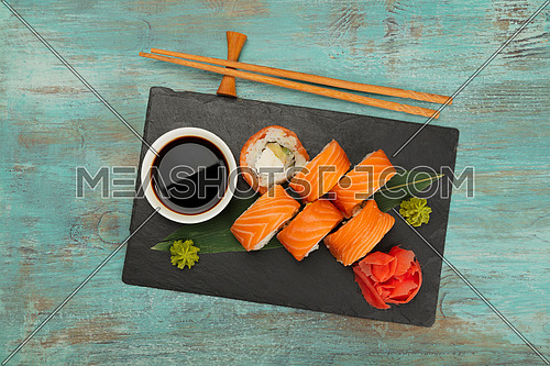 Close up set of six Philadelphia sushi rolls with raw salmon served on black slate board on blue table, elevated top view, directly above