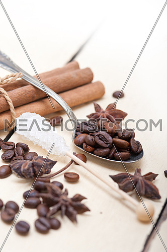 coffe sugar and spice on silver spoon over white wood rustic table