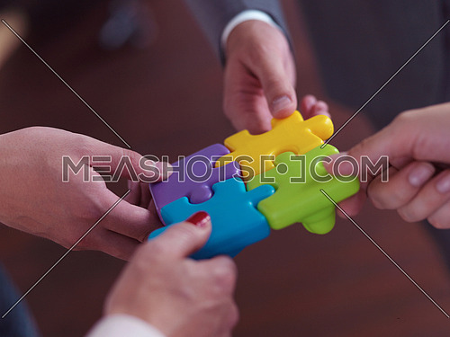 business people group assembling jigsaw puzzle and represent team support and help concept, top view at modern office interior