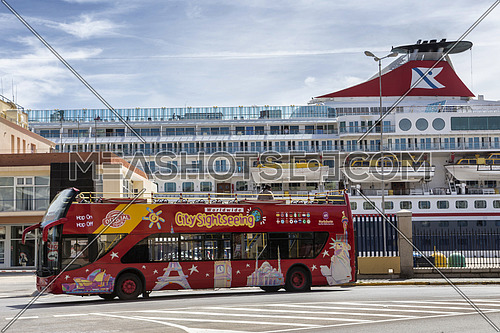 Cadiz Spain- April 1: Brightly decorated sightseeing double-decker open top bus in Cadiz takes visitors to all the major tourist attractions, near the port, in the background a Norwegian ferry docking at the pier, Take in Cadiz, Andalusia, Spain