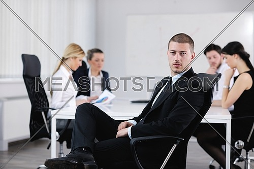 Portrait of a handsome young business man with people  in background at office meeting