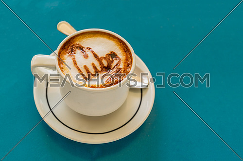 Capuccino on a cup with foam and above the foam the inscription Cuba on a background