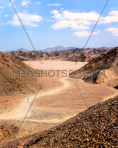 In the picture the Egyptian desert of stones with its mountains of many colors and man walking alone.