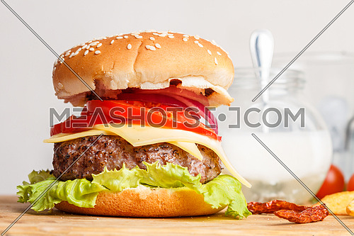 Burger sandwich on a wooden tray with garnish elements