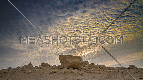 a big rock in the middle of the desert at a cloudy sunrise morning
