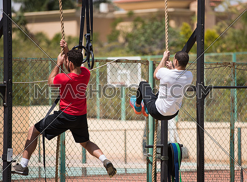 wo young middle eastern athletic built men strenuous exercise climbing the rope outside on a sunny day