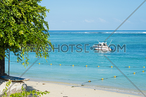 Fishing boat anchored near the shore of day beach,mauritius beach Flic and Flac.