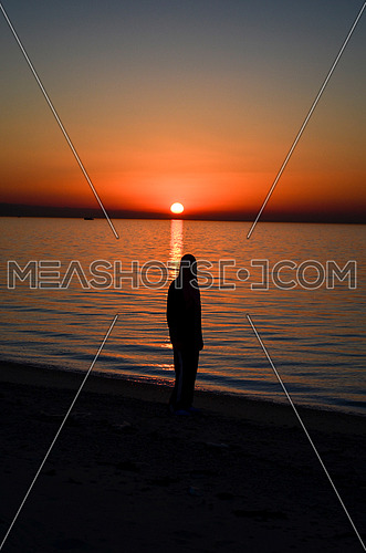 A girl standing on the beach during sunset magical hour