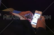 a close up on a man's hand looking through smartphone