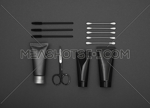 Neatly organized masculine beauty care and make up products flat lay over dark grey background, elevated top view, directly above